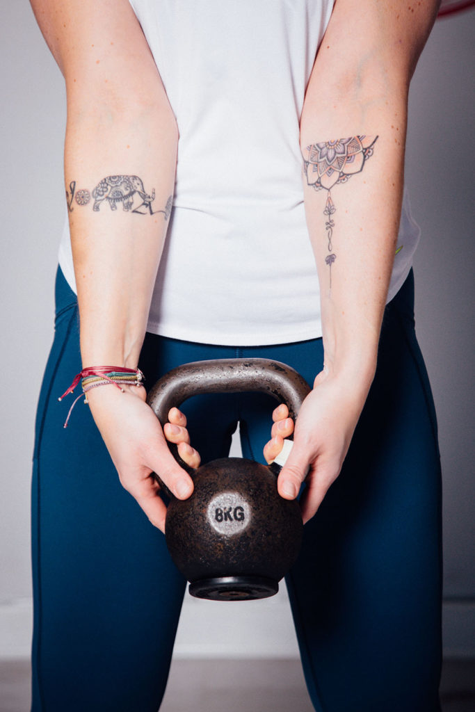 two arms with tatoos holding kettlebells