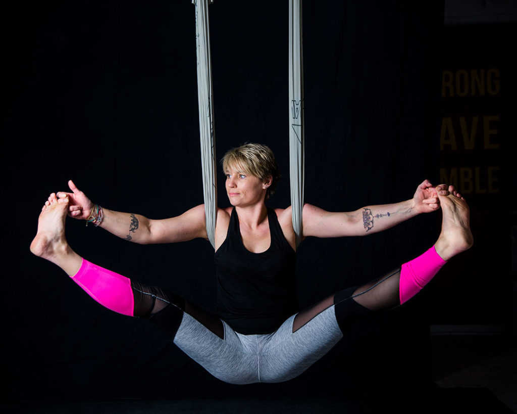 Anti-gravity yoga pose against black background -Brand Photography