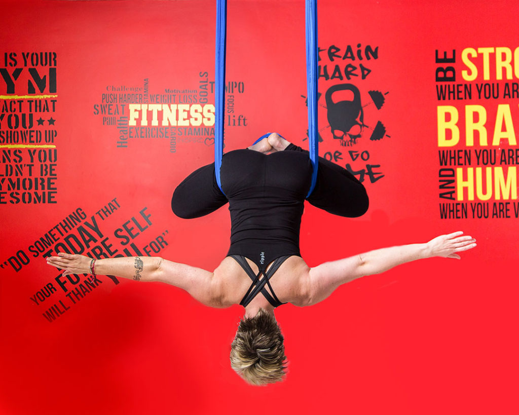 Anti-gravity yoga pose against a wall with graffitti - Brand Photography