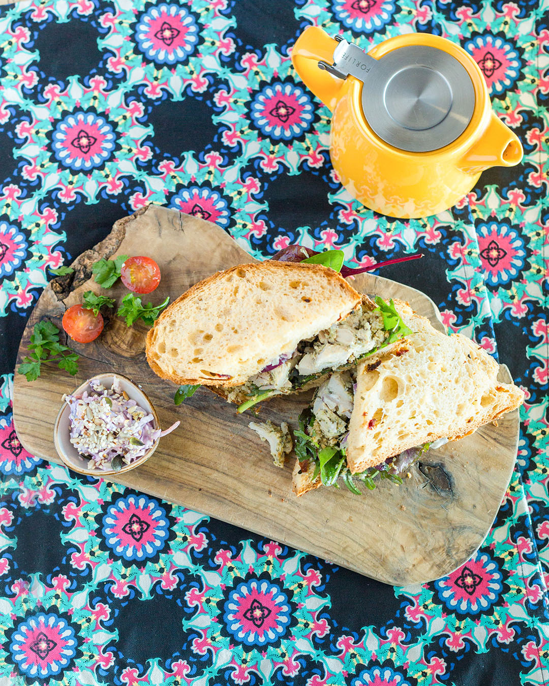 Sandwich on a board with on a brightly patterened table cloth and a yellow teapot - Personal Brand Photographer Dublin