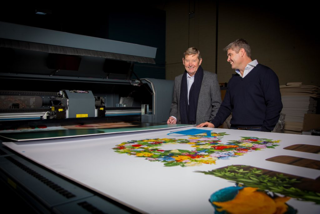 Two man behind a very big print-out