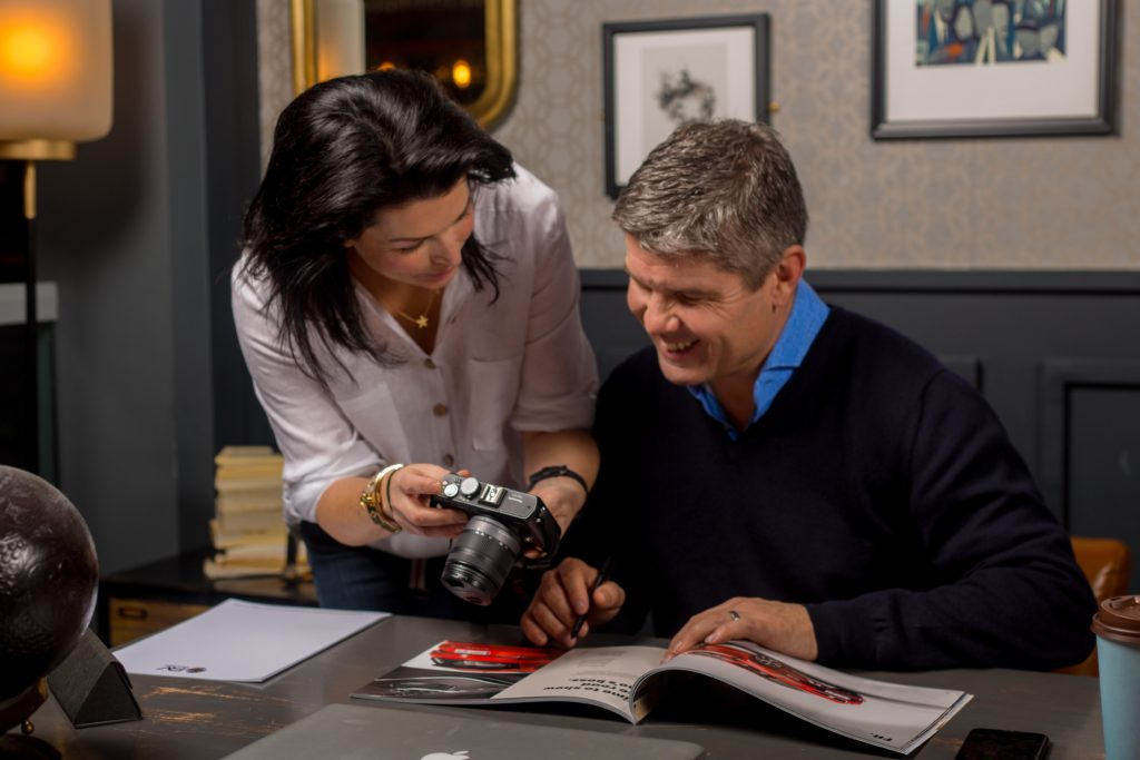 Lady showing a man the back of a camera in an office setting