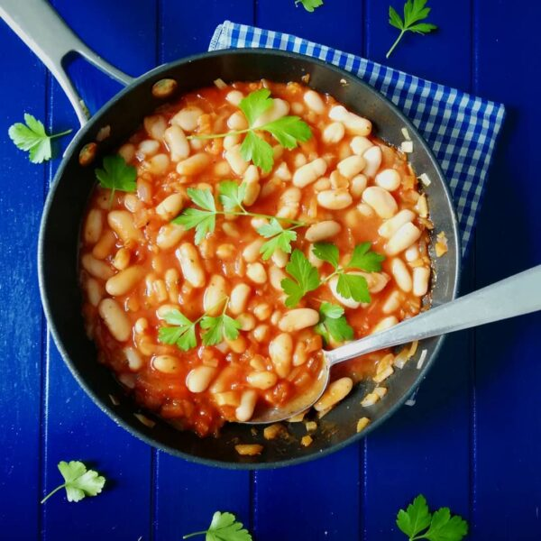 Food styling - pan with beans in tomato sauce with a blue background