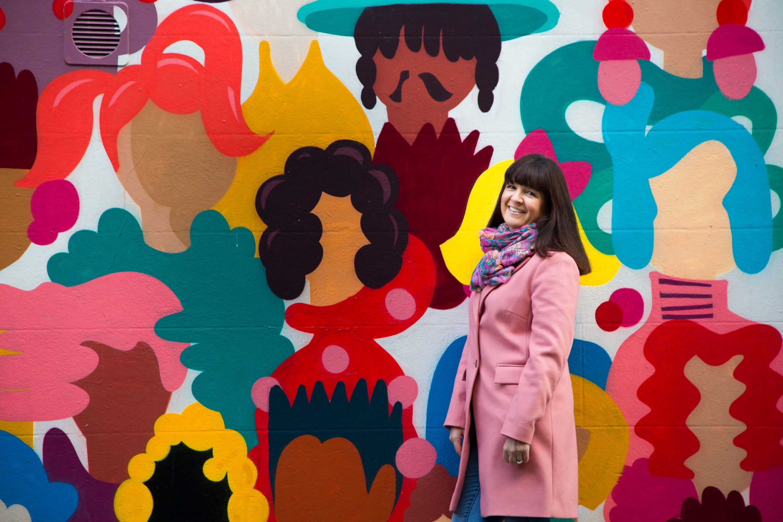 Lady in front of a colourful wall