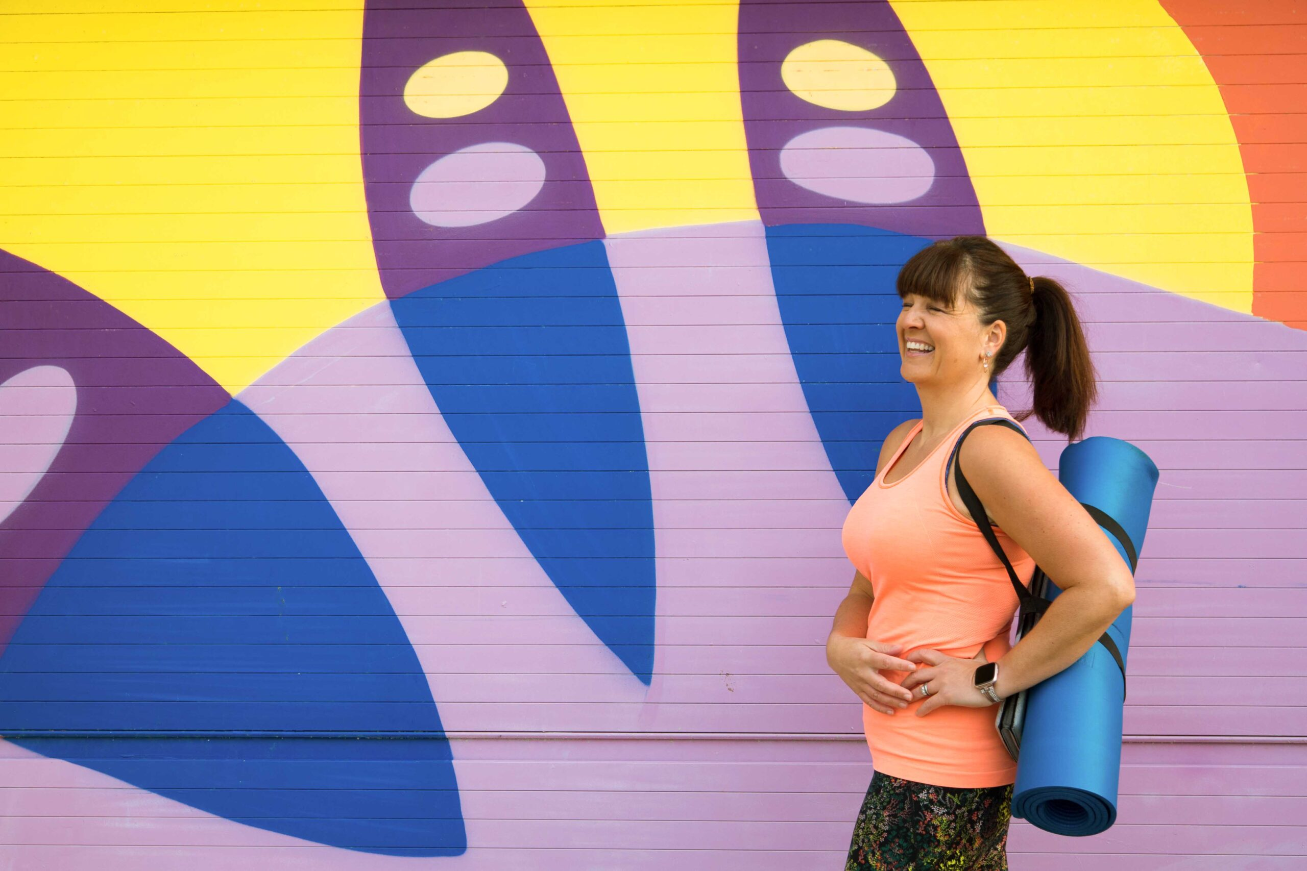 Lady with ilates mat in front of colourful wall